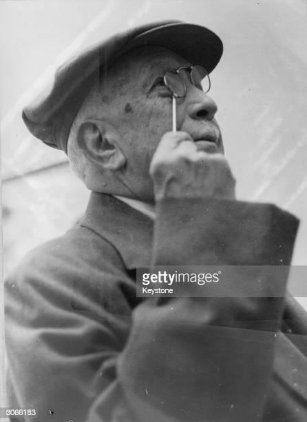 Composer Richard Strauss , composer of 'Der Rosenkavalier' and 'Salome' at the Bernese Art Gallery, Berne studying an exhibit through a pair of...
