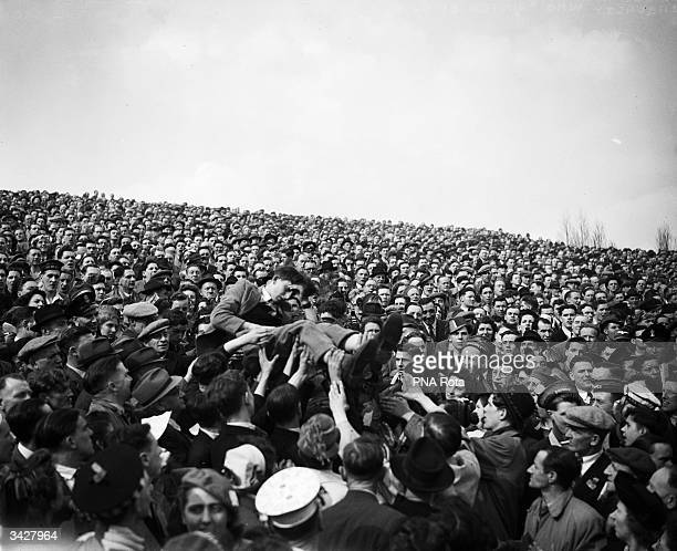 A casualty who fainted in the crowd is passed over the heads of the spectators at the FA Cup semifinal match between Portsmouth and Leicester City at...