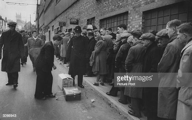 A policeman challenging a hawker selling wares to football fans queuing for tickets at Wolverhampton Wanderers 'Hawthorns' ground Original...
