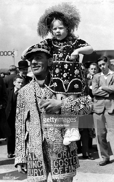 The Pearly King of Finsbury, J Marriot of Holloway, holding up his three year old daughter Jean at the Epsom Derby, Surrey.