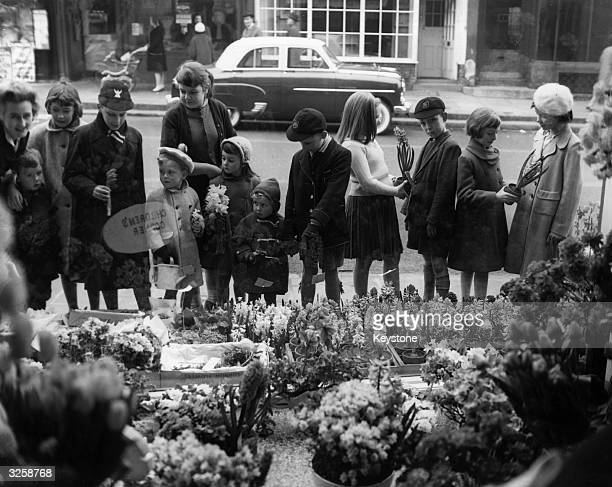 Children looking at the display for 'Mother's Day' in a flower shop in Highgate London