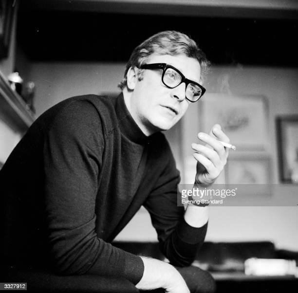 English actor Michael Caine smoking a cigarette.