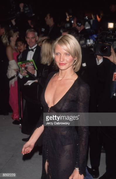 American actor Cameron Diaz smiles while walking in a sheer black Versace dress with a plunging neckline at the 'Vanity Fair' Oscar Party Morton's...