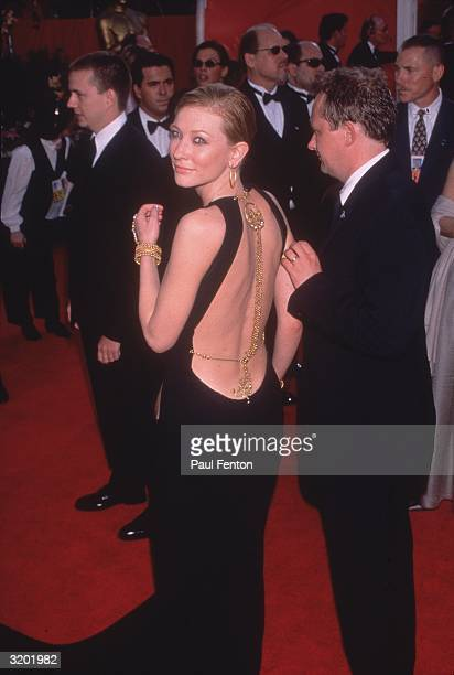 Australian actor Cate Blanchett smiles over her shoulder while walking with her husband Andrew Upton at the Academy Awards Shrine Auditorium Los...