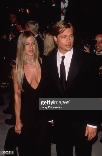 Engaged American actors Jennifer Aniston and Brad Pitt smile while posing together at the 'Vanity Fair' Oscar Party Morton's restaurant Beverly Hills...
