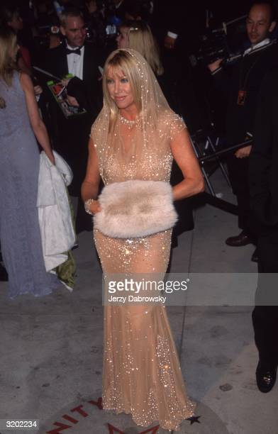 Fulllength image of American actor Suzanne Somers holding a faux fur muff in a nudecolored diaphanous hooded dress with strategically placed sequins...