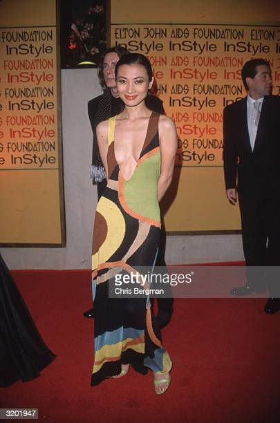 Fulllength image of Chinese actor Bai Ling wearing a formfitting brightly colored dress with a plunging neckline at the Elton John/'In Style' Oscar...