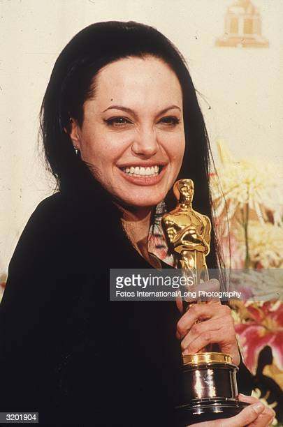 Headshot of American actor Angelina Jolie grinning and holding the Oscar she won for Best Supporting Actress in director James Mangold's film 'Girl...