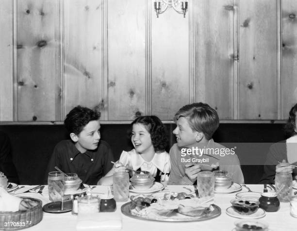British child actor Freddie Bartholomew and his American colleague Mickey Rooney enjoy some ice cream and a joke with the child star Peggy Ryan