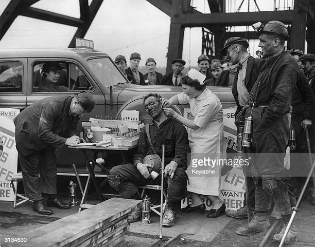 A mobile blood transfusion van parked at a south Yorkshire colliery where the miners have volunteered to give blood A nurse performs a blood test on...