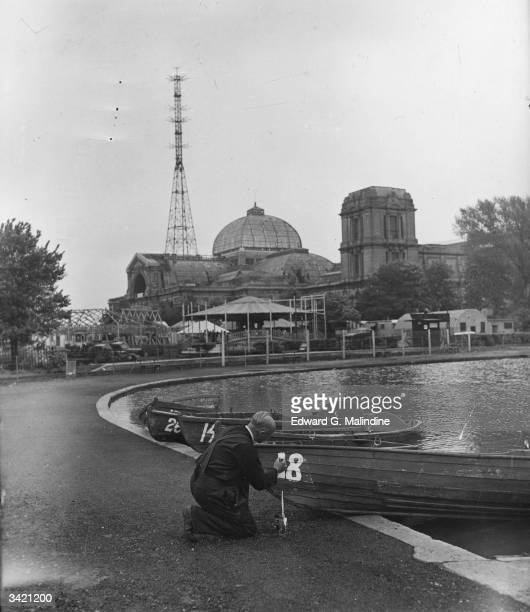 A boatman painting numbers onto boats at a lake in the grounds of Alexandra Palace London