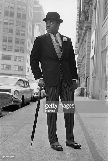 American Heavyweight boxer Cassius Clay in New York dressed like a city gent in a suit and a bowler hat and carrying an umbrella