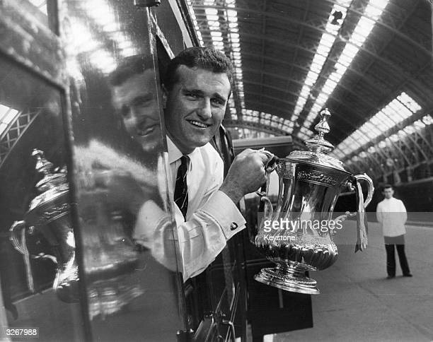 Manchester United captain Noel Cantwell holds the FA Cup trophy out of the window of the train before leaving for Manchester after a 31 victory in...