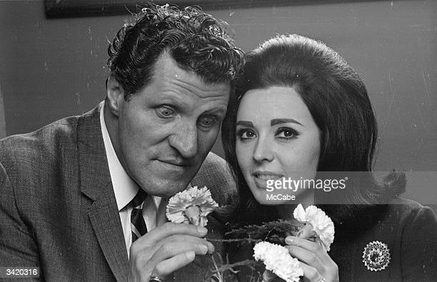 British comic Tommy Cooper investigating a bunch of carnations with pop singer Susan Maughan most famous for her hit 'Bobby's Girl'