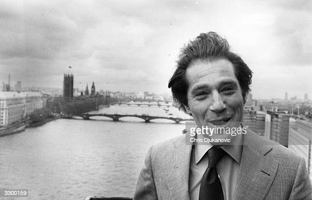 American actor and film star George Segal on a visit to London. Parliament buildings and several bridges can be seen in the far background.