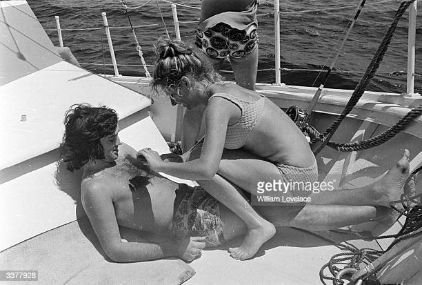 Professional footballer George Best being massaged by a young woman on a yacht at sea