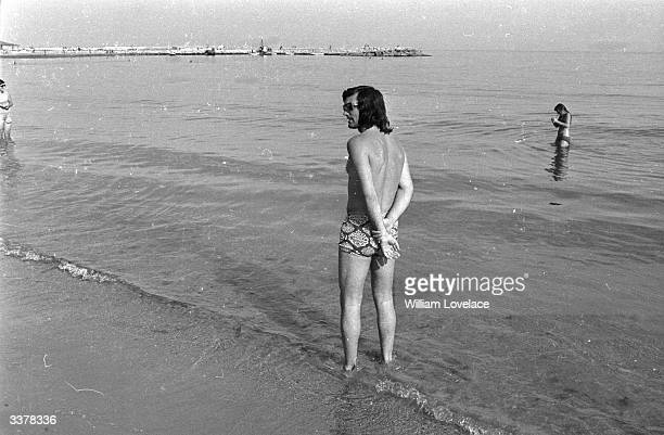 Professional footballer George Best paddling on a sea shore on a summer's day