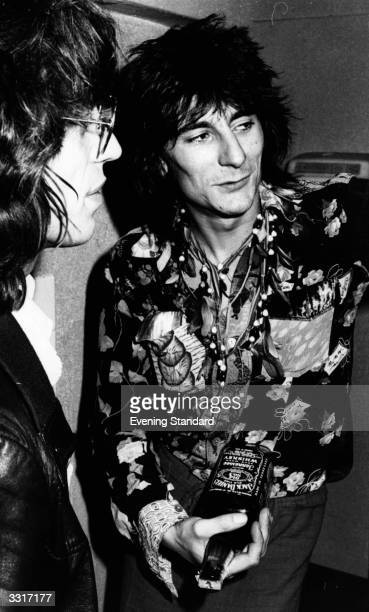 British rock singer Mick Jagger, left, and guitarist Ronnie Wood of the Rolling Stones, holding a bottle of Jack Daniels.