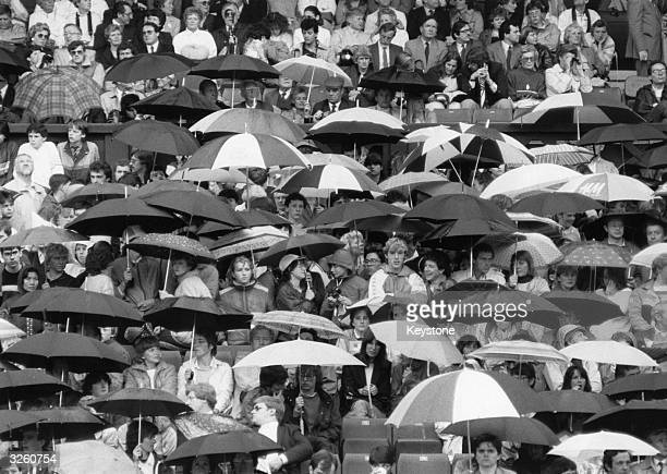 Spectators sheltering under umbrellas as rain stops play at the Wimbledon tennis championships