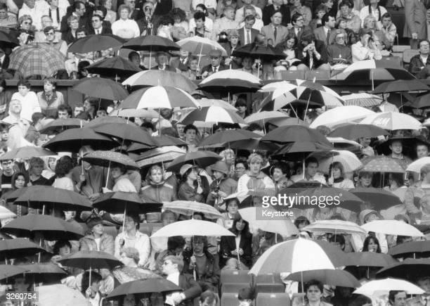 Spectators sheltering under umbrellas as rain stops play at the Wimbledon tennis championships