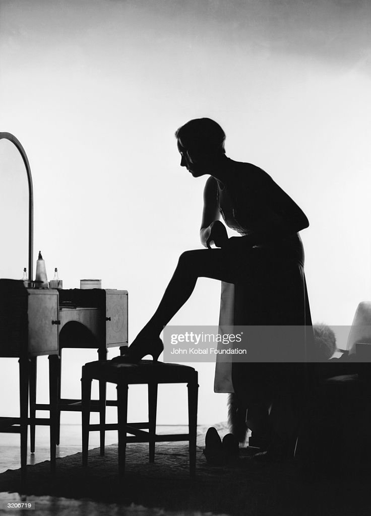 A silhouetted woman fastens her stocking in front of her dressing table.