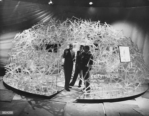 US designer William Burton inside a model of a section of a human life cell which he designed He is talking to Raymond Baxter of the BBC and...