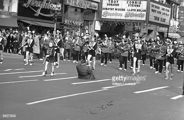 A man squats in the street to photograph a brass band and majorettes marching in the Thanksgiving Parade near Times Square New York