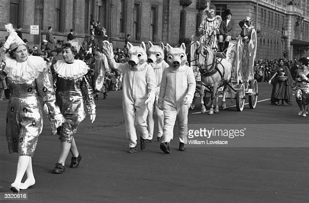 Costumed participants in a New York Thanksgiving Day Parade Some are dressed as pigs others as harlequins