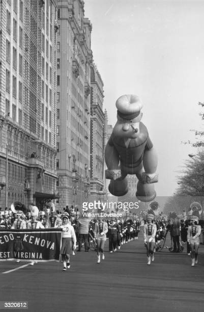 Popeye floats above a band and drum majorettes from West Virginia in a Thanksgiving day parade in New York