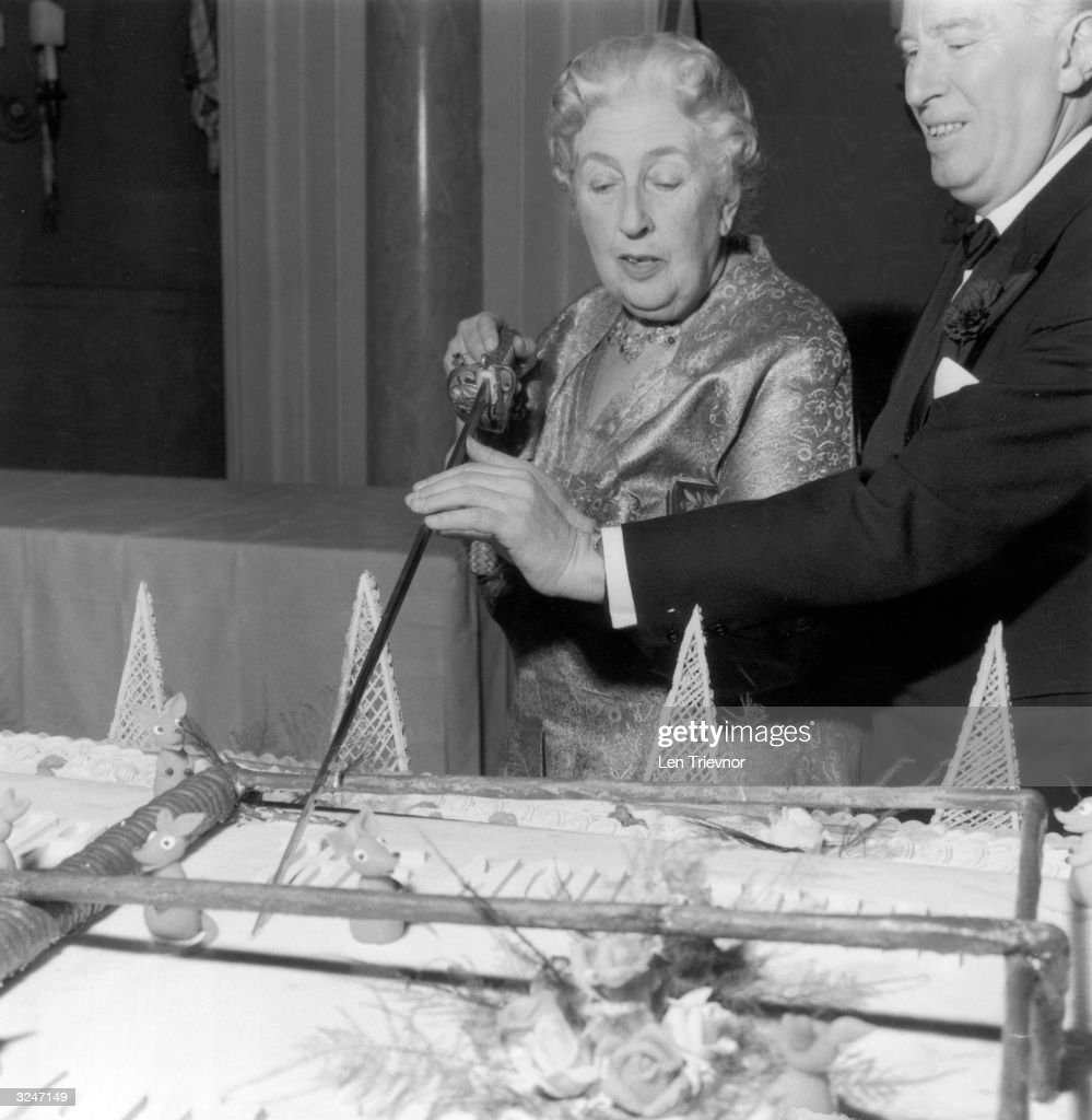 Mystery writer Agatha Christie (1890 - 1976) cuts an enormous cake at a party to celebrate the 10th anniversary of her long-running play, 'The Mousetrap'.