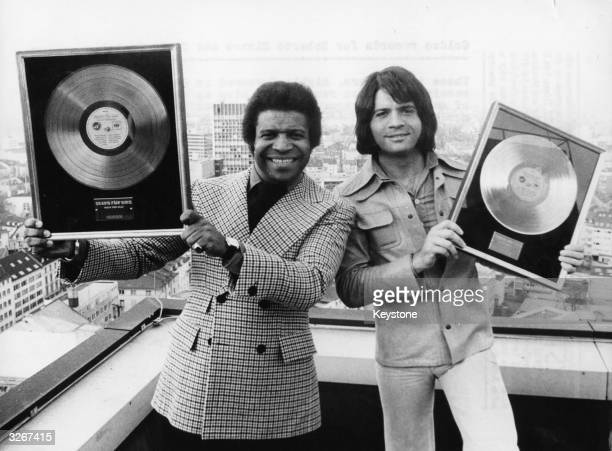 Latin pop singers Roberto Blanco and Costa Cordalis both highly favoured in Germany hold up golden discs they were awarded in Frankfurt for sales of...