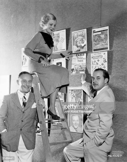 Songwriting partners, lyricist, Arthur Freed and composer, Nacio Herb Brown with a display of the sheet music covers of some of their songs,...