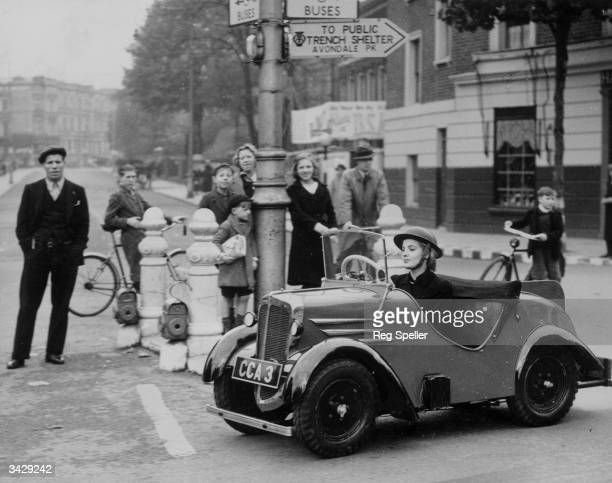 A woman driving the new solution to the problem of wartime petrol rationing the midget car This tiny vehicle can cover eighty miles on a gallon of...