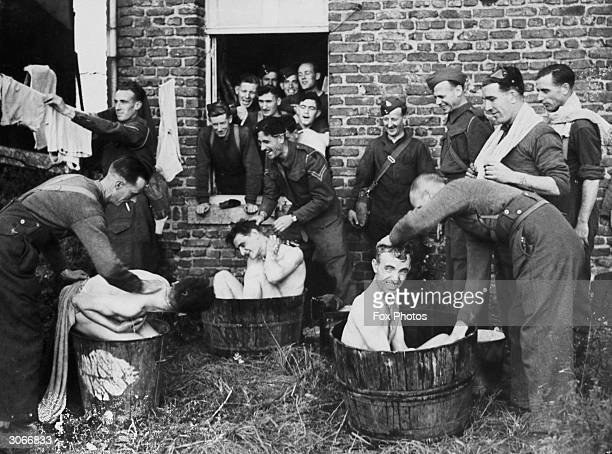 British soldiers serving in France during World War II make do with a wooden tub filled with water when it comes to bathing