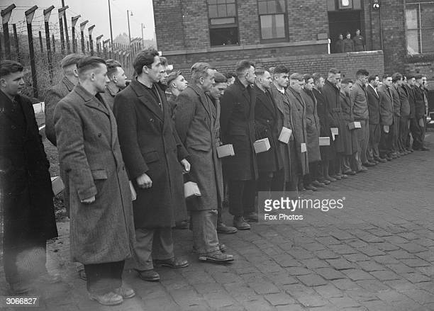 German prisoners-of-war line up at a POW camp situated in a disused mill in the north of England.