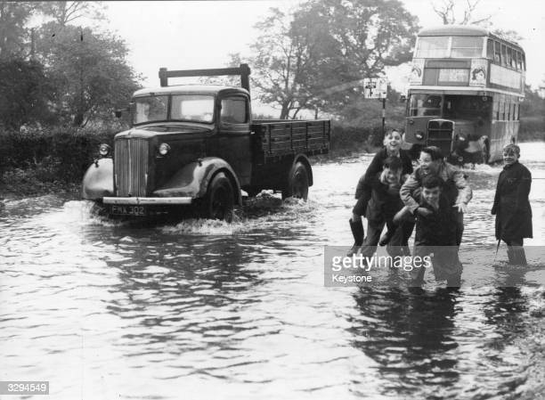 A group of Greenford schoolboys frolic in the flooded Ruislip Road