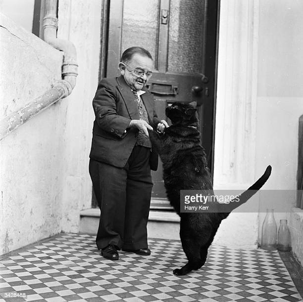 Henry Behrens the smallest man in the world dances with his pet cat in the doorway of his Worthing home Measuring only 30 inches high Mr Behrens has...