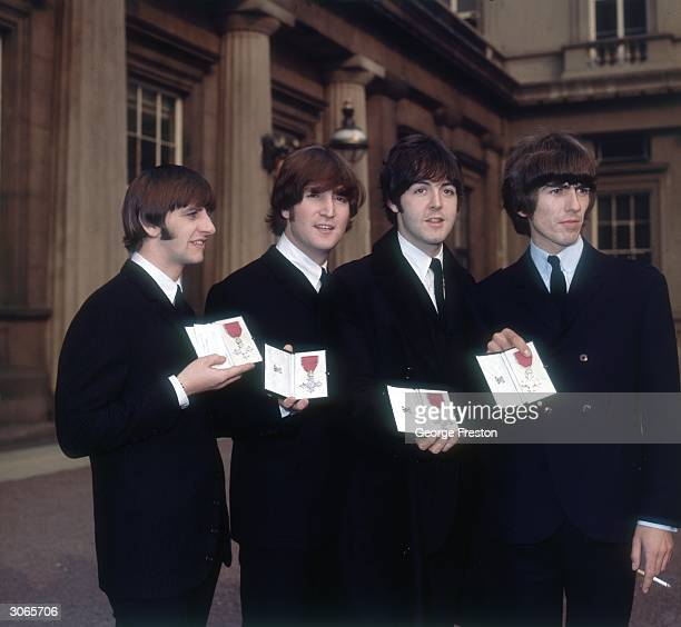 British 1960's rock band the Beatles holding their MBEs after an investiture ceremony at Buckingham Palace in London From left to right John Lennon...