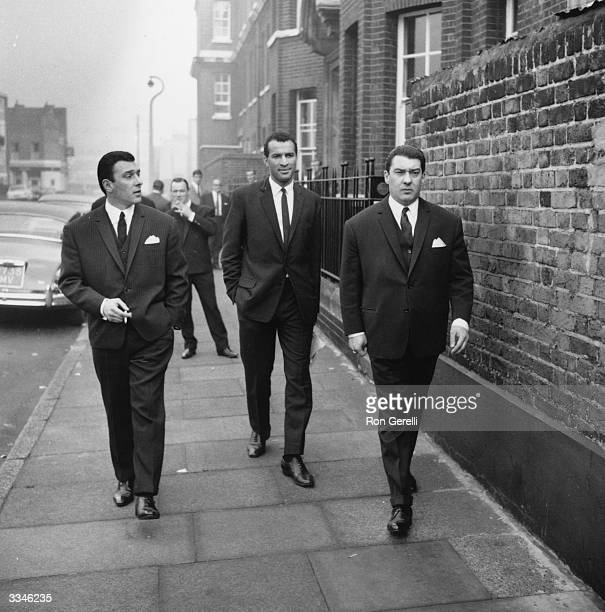 London gangsters Ronnie and Reggie Kray walking along an East End street London