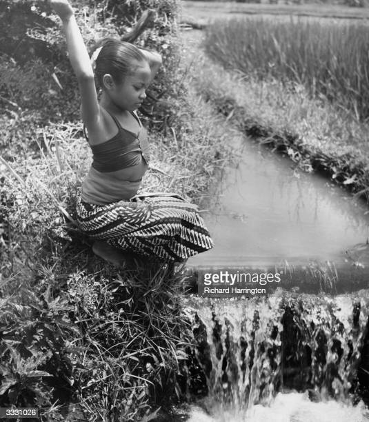 A Balinese child unties her long black hair by a stream Everywhere in Bali the sound of running water can be heard from creeks and irrigation channels