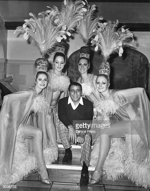 American singer Tony Bennett with some of the dancing girls who appear in his show at the London Palladium