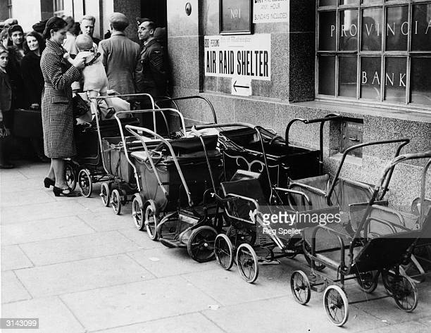 People waiting to enter a bank in London which converts into an air raid shelter after working hours.