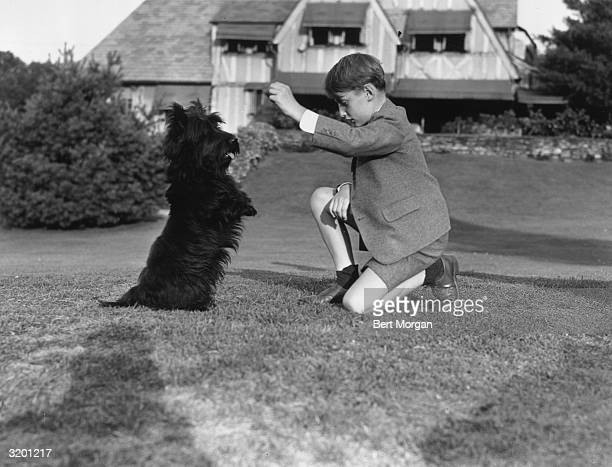 EXCLUSIVE Prince Harald of Norway kneels on the ground with one hand raised as US president Franklin D Roosevelt's Scottish terrier Fala sits on its...