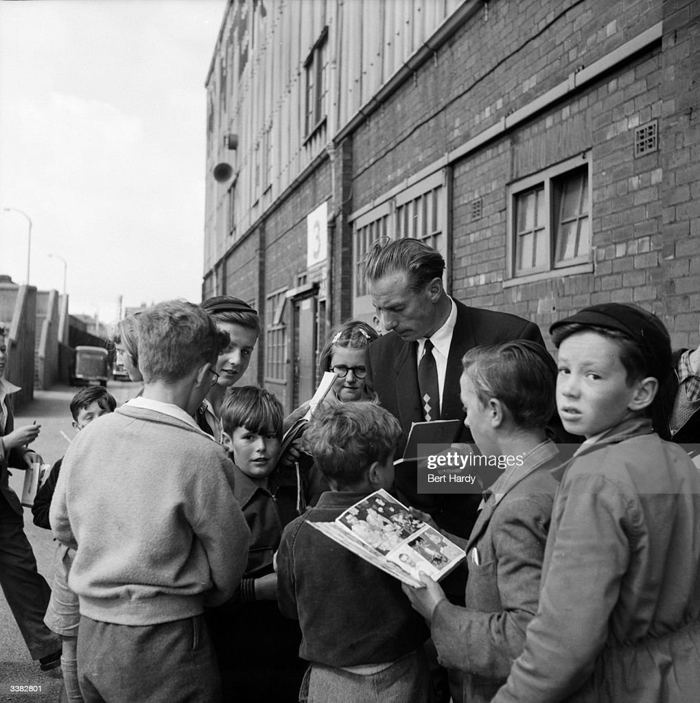 Blackpool Football Club player and household name, Stanley Matthews, signs autographs for young fans outside Blackpool's ground. After all these years in the game, the country's most famous footballer still finds crowds 'embarrassing'. Original Publication: Picture Post - 6721 - Stanley Matthews, The Hero At Home - pub. 1953
