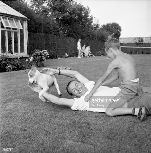 Britain's most famous footballer Stanley Matthews of Blackpool FC plays in the garden of his Blackpool home with his son Stanley Junior and Bobby the...