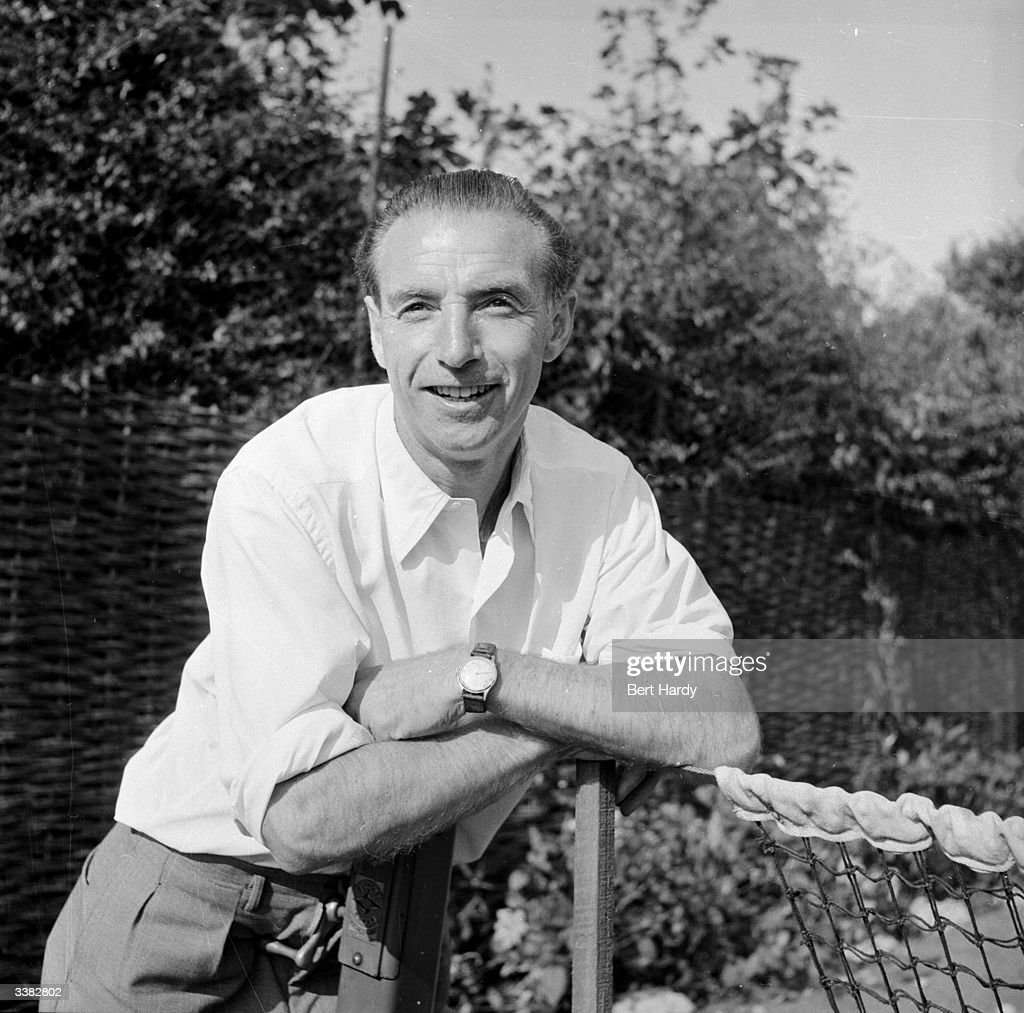 Stanley Matthews, 38-year-old Blackpool Football Club player and household name, relaxes at the lawn tennis court in the garden of his Blackpool home. Original Publication: Picture Post - 6721 - Stanley Matthews, The Hero At Home - pub. 1953
