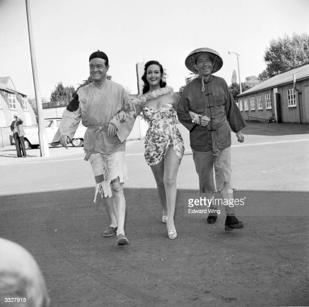 Comedian Bob Hope , actress Dorothy Lamour and film star and singer Bing Crosby walking arm-in-arm at Shepperton Studios during the filming of 'Road...