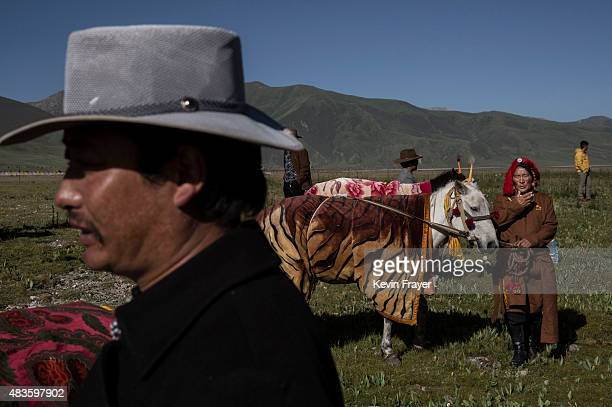 Tibetan nomads stand with their horses before a race at a local government sponsored festival on July 26 2015 on the Tibetan Plateau in Yushu County...