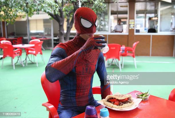 Year-old Burak Soylu with his Spider-Man costume eats his meal as he performs in Antalya, Turkey on November 4, 2019. Burak Soylu, who has worked at...