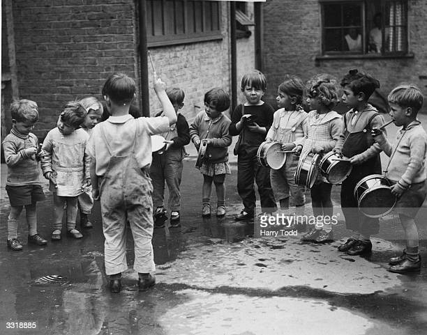 Children at the Chelsea OpenAir Nursery School in Glebe Place wait for one of their colleagues to mend his instrument before continuing with their...